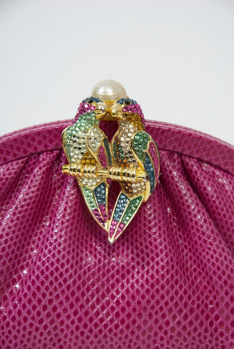 Judith Leiber convertible clutch/shoulder bag in a vibrant shade of pink karung featuring a double parrot clasp bejeweled with complementary crystals and topped with a large pearl. Matching fabric interior fitted with the usual Leiber accoutrments -