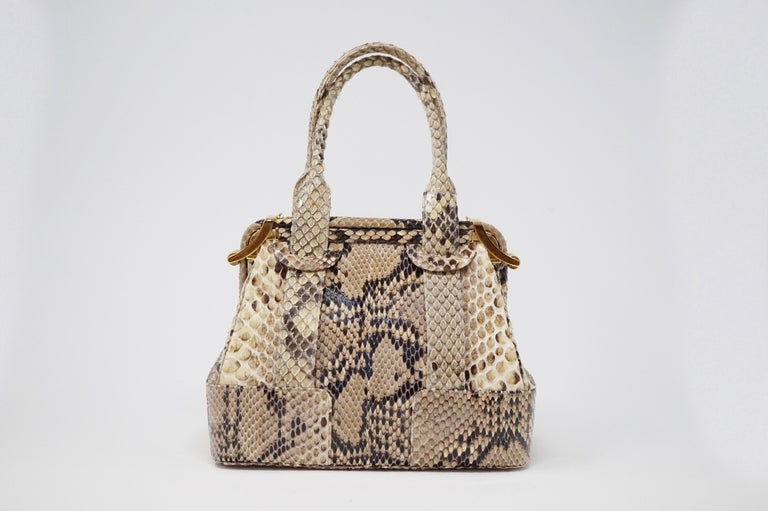 This gorgeous and rare Judith Leiber Python Structured Frame Handle Bag is crafted with luxurious genuine natural python and features two top handles and gold-tone hardware.   The side clasp closures opens to a grosgrain fabric-lined interior with