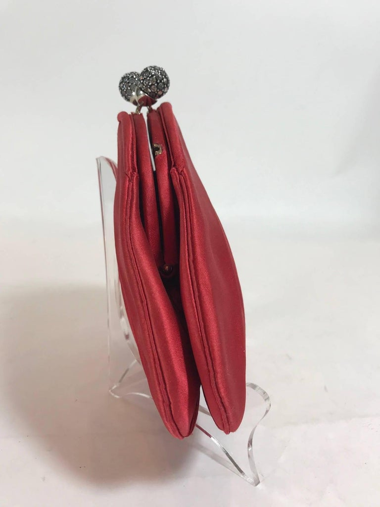Red satin Judith Leiber evening bag enhanced by silver-tone hardware and a rhinestone encrusted kiss closure clasp. Red satin interior. Original Shoulder Strap included.