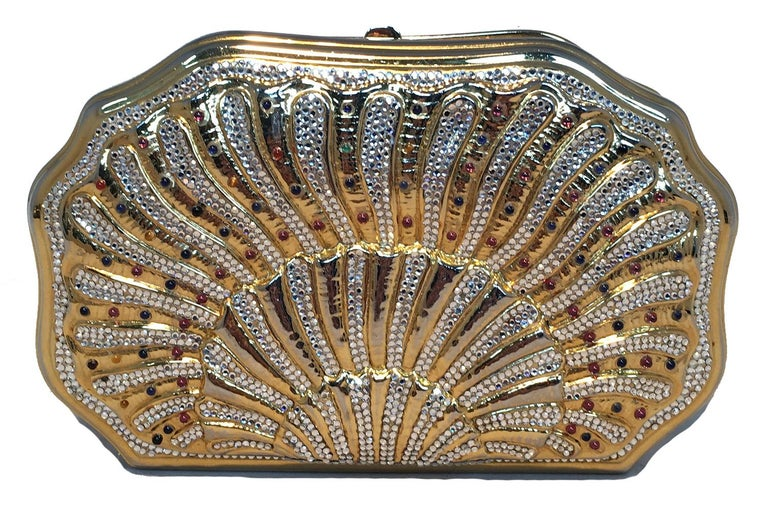 Judith Leiber Swarovski Crystal Gemstone Shell Minaudiere Evening Bag in excellent vintage condition. Gold shell shape with clear swarovski crystals and tiny multicolor gemstone details. Top button closure opens to a gold leather interior that holds