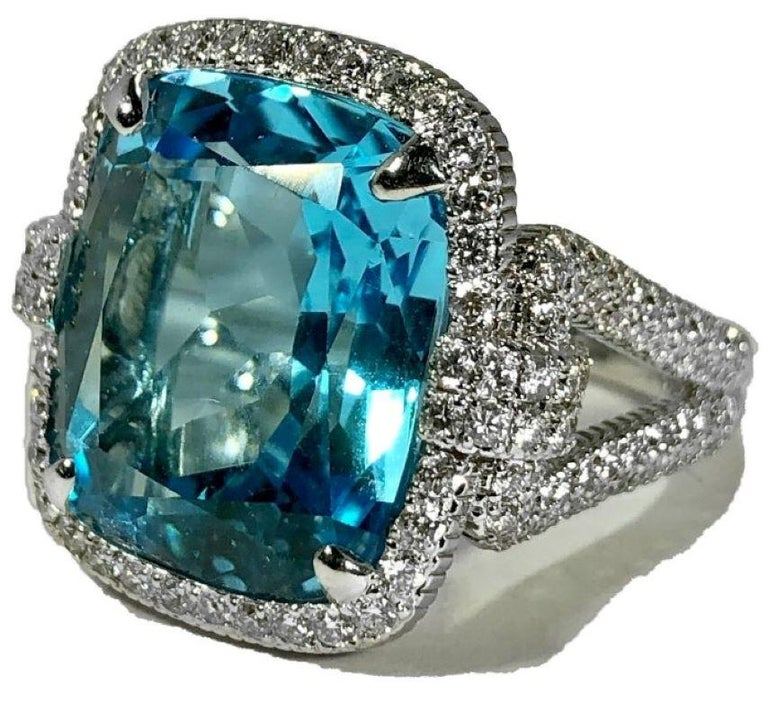 This wonderful JUDITH RIPKA designed 18k white gold ring has, at it's center, one  striking  natural blue topaz which is surrounded by a bezel and flanked by shoulders all of which are heavily diamond encrusted. The topaz is brilliant and large,