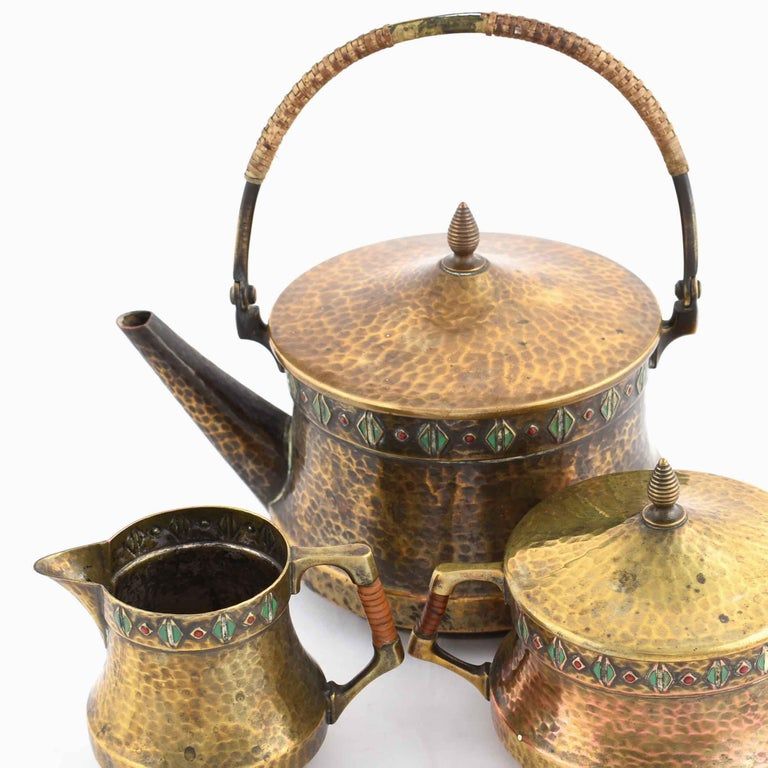 Jugendstil tea set is an original group of decorative objects realized in the 1910s.  Original decorated brass.  Realized by WMF. Made in Germany.   The set includes: a coffee pot, a sugar bowl and a cream server.  Very good conditions.