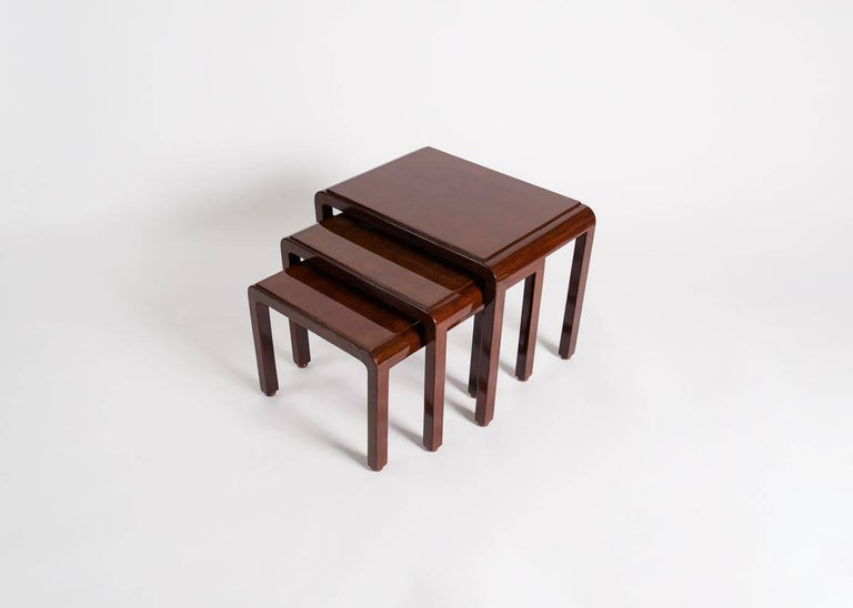 Stamped.  One of a number of collaborations between the French designer and Japanese lacquer master, these tables, a set of three with rectangular tops and rounded corners, fit snugly each with the others, and exhibit the respective skills of each