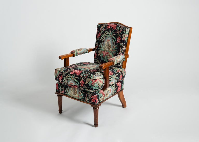 This remarkable pair of late Deco armchairs possess many of the beautiful aesthetic trappings of Jules Leleu's most famous 40s designs, and are clad in an elaborate, wildly colorful upholstery.  Stamped: Leleu Paris, Made in France  Numbered: