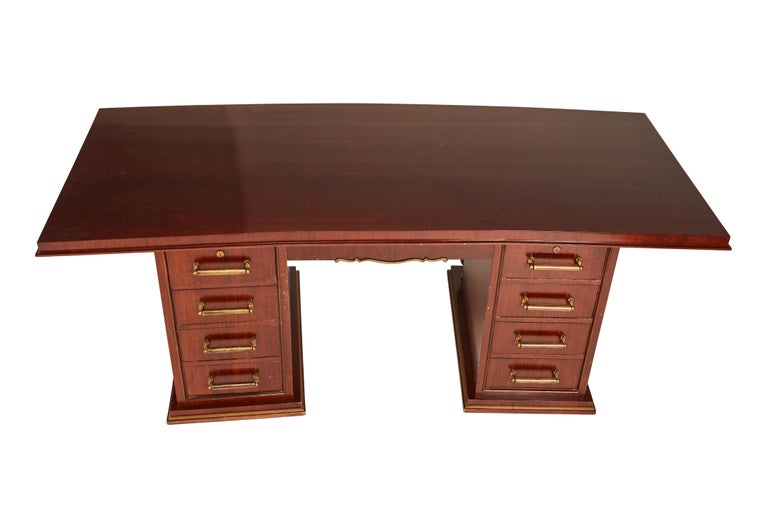 Jules Leleu (1883-1961) double-fronted mahogany and brass desk, circa 1935. Having two set of four pedestal drawers and a single frieze drawer, accented in gilt bronze. Inset with plaque J. Leleu.... no key. Wear to finish on top and drawers, to