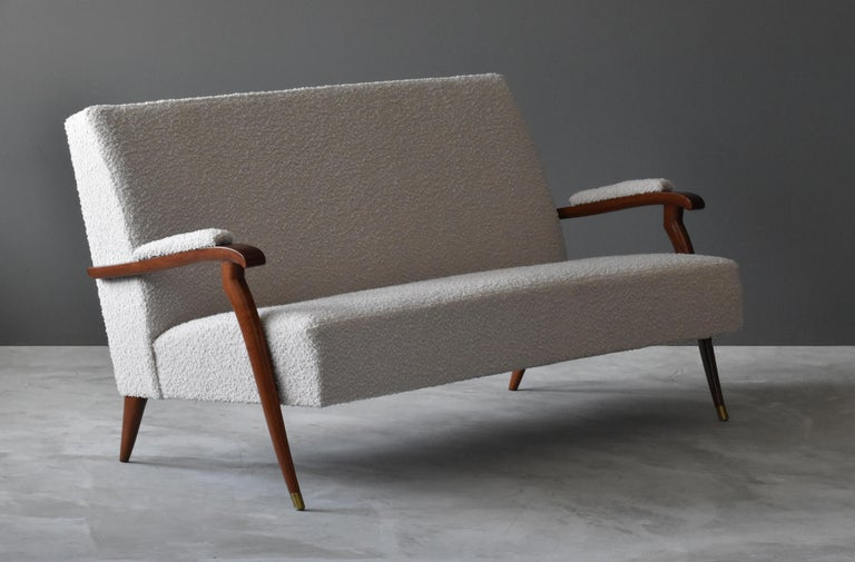 A modernist settee, sofa or loveseat. Designed by Jules Leleu in the 1960s and produced by his own firm, Maison Leleu.   Executed in lacquered mahogany, brass, and new high-end bouclé fabric.  Literature: Sirex, The House of Leleu, 2008, p.