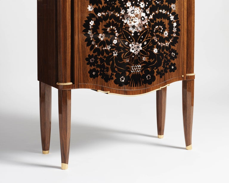 An exceptional, rare mahogany cabinet made by Jules Leleu the year after the war, featuring gilt bronze details and ornaments, and an elaborate, mother-of-pearl and ebony inlay by Messager.