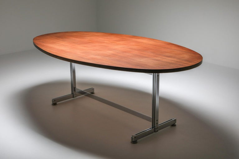 Jules Wabbes oval dining table for Mobilier Universel, circa 1960, Belgium. Rosewood veneered top; chrome-plated steel base. Dimensions: W 200 cm, D 120 cm, H 75 cm.