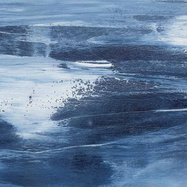 This coastal abstract statement painting is made with acrylic paint on a large-scale canvas. The artist uses broad strokes of paint to layer light, muted blues, greys, and white on top of a deeper blue which can be seen at the bottom of the