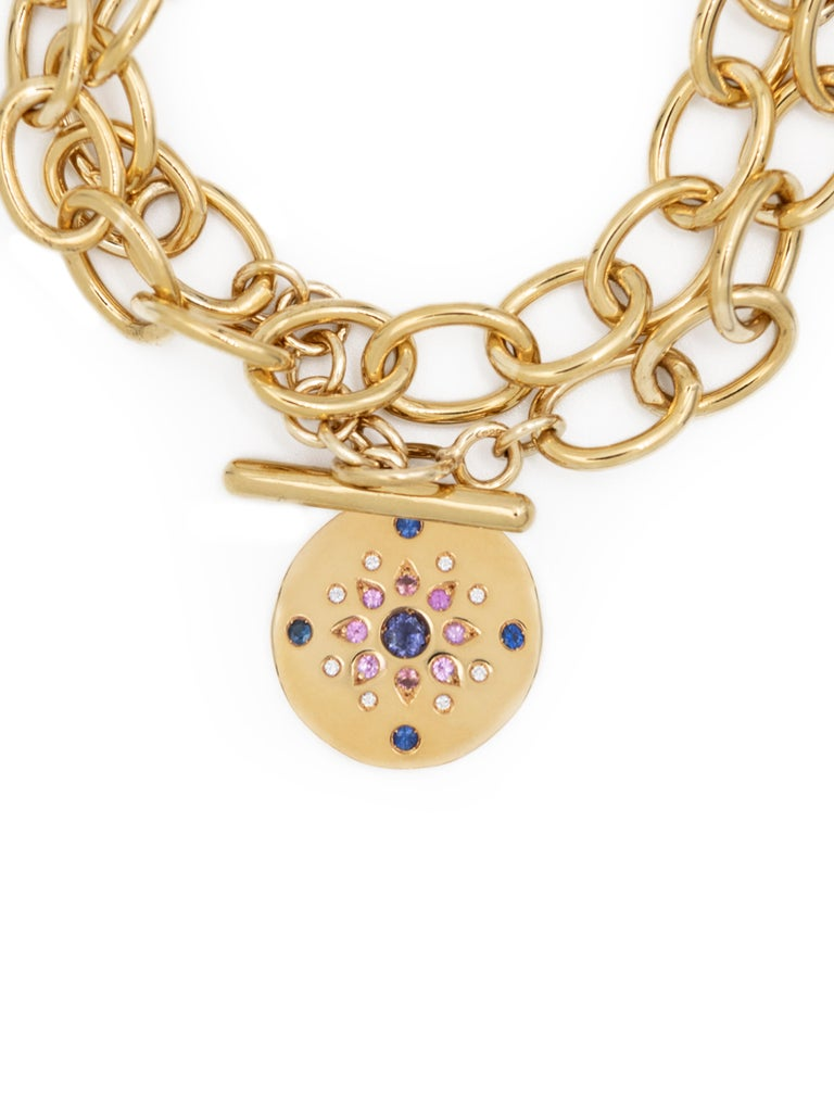 18 karat yellow gold bracelet with round disc pendant and large chain that wraps around the wrist twice. The pendant is set with 21 gemstones including 0,16-carat of blue sapphire and 0,33-carat of diamonds.   Please note that the bracelet described