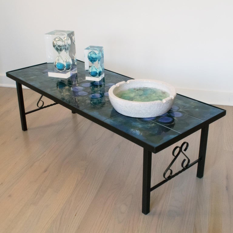 Elegantly crafted Mid-Century Modern coffee or side table designed by Belgian artist Juliette Belarti in the 1960s. This cocktail table features an eye-catching ceramic tiles top using a rare turquoise-blue color that creates a beautiful contrast
