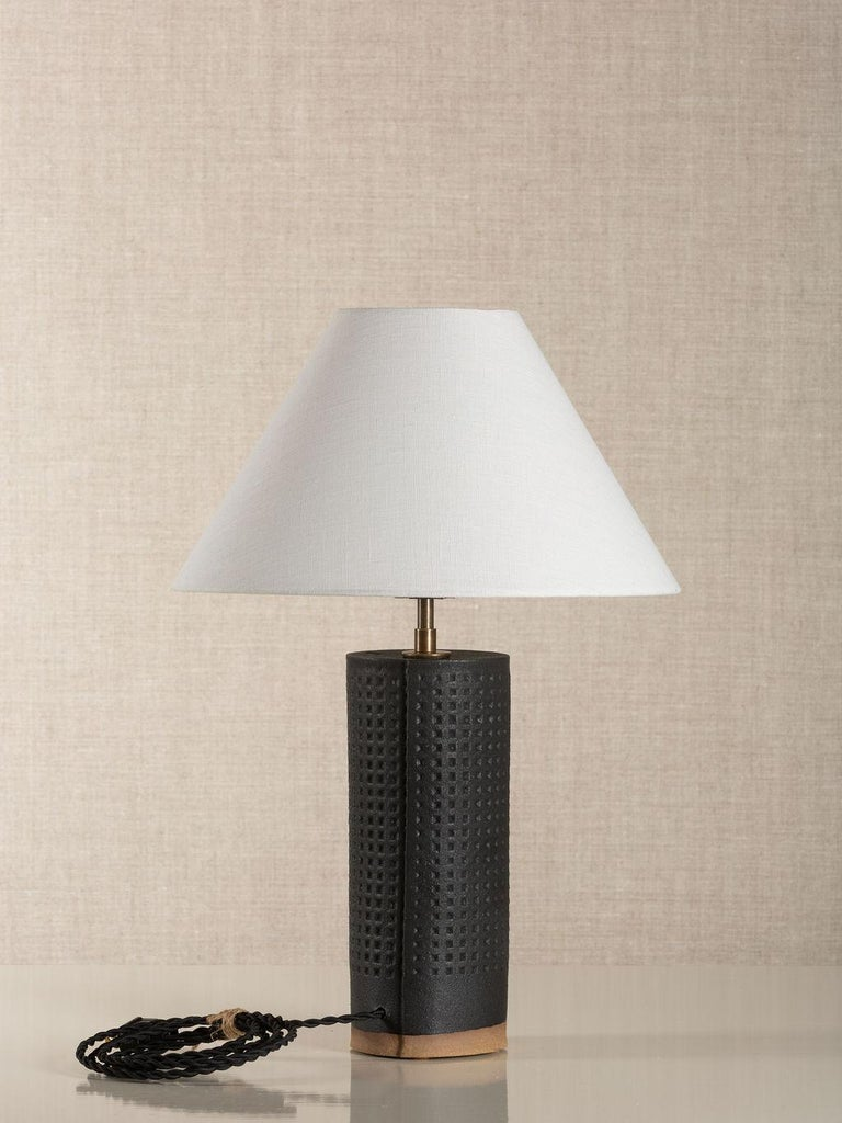 Handmade stoneware slab construction with waffle texture. Lamps are individually crafted and one of a kind.  Finish  Matte Black glaze with waffle texture. Antique brass fittings with a dimmer switch on the socket and a braided black cloth cord.