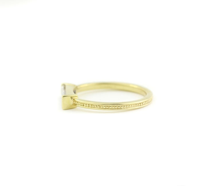 18 Kt Yellow Gold and Baguette Diamond Ring  This unique ring blends the ancient style of a finely beaded band detail with the modern setting of one long, baguette Diamond (10.3mm x 3mm).  This clear and unusually cut Diamond weighs .54 Cts. and is