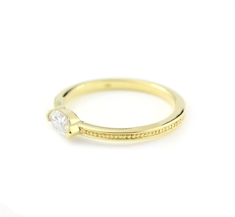 18 Kt Yellow Gold and Marquise Diamond Ring  This ring blends the ancient style of a finely beaded band detail with the modern setting of one Marquise Diamond (.34 Cts.).  The Diamond is clear and bright, measuring 6.7mm x 3.5mm and rated