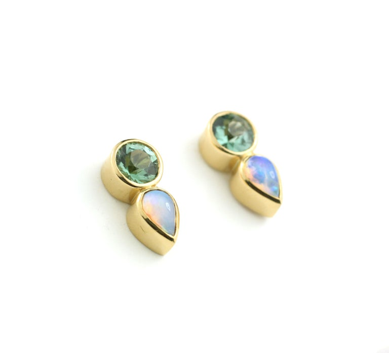 These stud earrings are made special by the unique pairing of two round, faceted, mint green Tourmalines of exceptional brightness (1.01 Cts.) with two fiery, pear shape Opals (.46 Cts.).  Bezel set in 22Kt Gold with 18 Kt Gold posts and backs, for