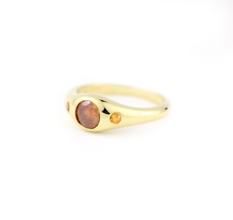 This One-of-a-Kind Sun Ring contains 1 Natural Color Diamond and 2 Orange Sapphires.  The diamond is an unusual orange color natural diamond weighing .60 Cts. and is flanked in a solid 18 Kt Gold mounting by two sweet, light orange Sapphires (.10