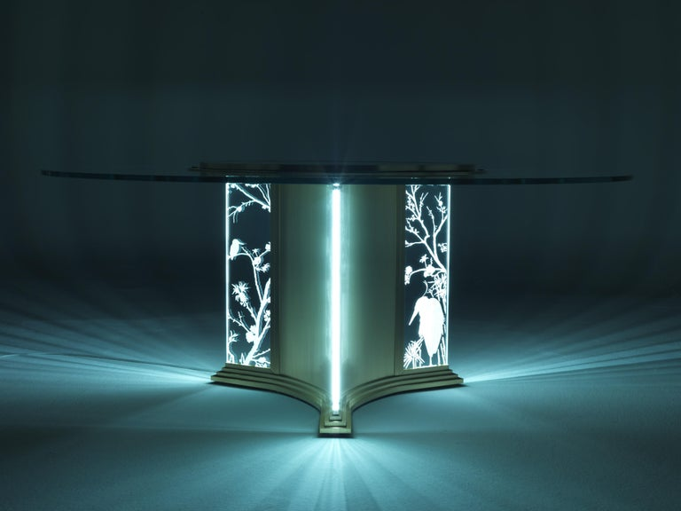 The lighting takes place through the thickness of the glass highlighting the engraved elements: bamboo, herons, peach blossoms and other elements inspired by the Oriental tradition.  Materials: Dining table with structure in brass and engraved