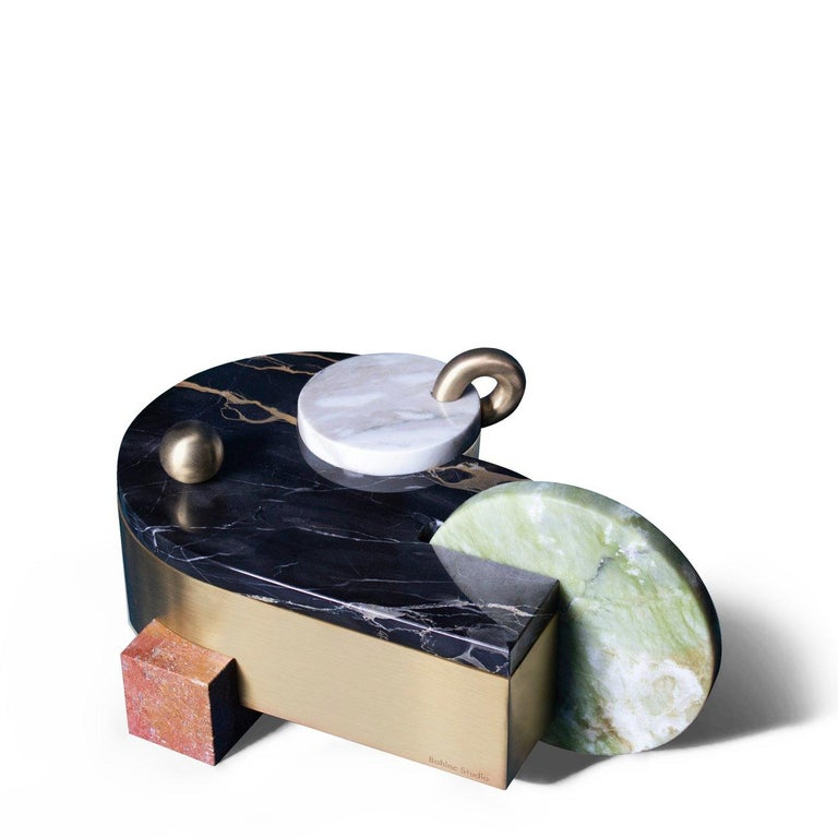 Bohinc Studio's new Juno box comprises a large brass body and a smaller round compartment. Details in green ming, red travertine, calcatta and portoro marbles add a playful, almost feminine, touch to the otherwise predominantly geometric