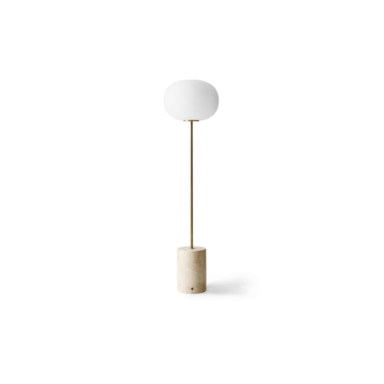 The JWDA floor lamp is part of a collection of lighting inspired by traditional oil lamps. Crafted from contrasting materials, the elegant yet bold design is a lesson in refinement and a study in geometry. An elliptical opal glass shade, a slender