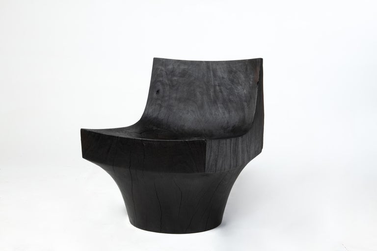 Made of charred Almendro wood salvaged from trees that fell during the devastation of Hurricane Maria in Puerto Rico, the K chair is carved by hand from a single piece of solid wood. Created by Reynold Rodriguez's design studio in San Juan, PR.