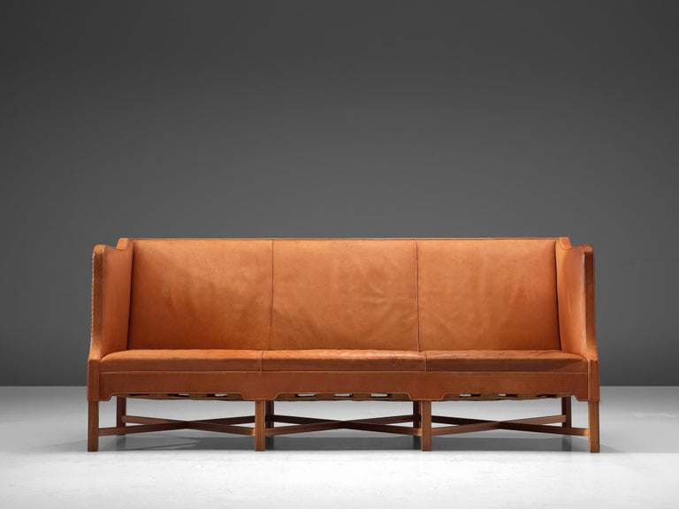 Kaare Klint for Rud Rasmussen, sofa model 4118, in leather and mahogany, by Denmark, 1929, made in 1950s.  Classic and elegant Scandinavian three-seat sofa by Kaare Klint. This model was designed in 1929. The base consist of eight legs in mahogany