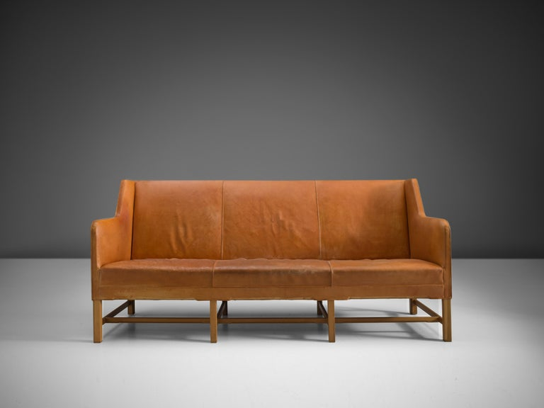 Kaare Klint for Rud Rasmussen, sofa model 4118, leather, wood, Denmark, design 1929  Classic and elegant Scandinavian three-seat sofa by Kaare Klint designed in 1935. The high back is structured by vertical lines into three parts that flow over into
