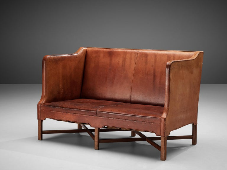 Kaare Klint for Rud Rasmussen, sofa 4118, original leather, mahogany, Denmark, 1930s  Classic and elegant Scandinavian two-seat sofa by Kaare Klint for manufacturer Rud Rasmussen. The piece is upholstered with patinated original leather. The base