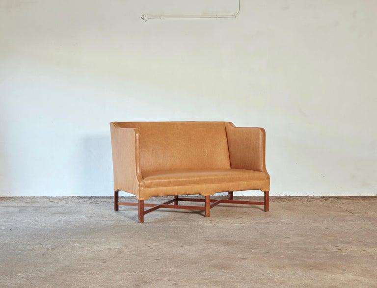 Rare Kaare Klint Model 4118 two-seat box sofa with profiled cross legged mahogany frame. Made by Rud Rasmussen, Copenhagen, Denmark. Upholstered in cognac leather.  Measures: H 87 cm, W 135 cm, D 70 cm.