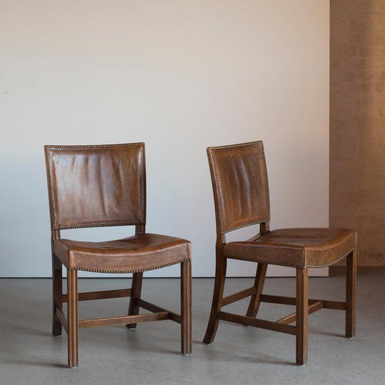 Kaare Klint pair of red chairs, oak, ox-hide and brass. Executed by Rud. Rasmussen, 1950s.  Reverse with paper label 'RUD. RASMUSSEN/SNEDKERIER/45 NØRREBROGADE/KØBENHAVN.
