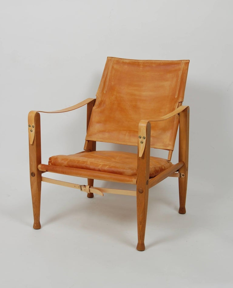 Patinated leather and oak frame Safari lounge chair originally designed in 1933 by Kaare Klint, regraded as the father of the Danish modern style. Leather strap arms and a tilting back rest for comfort with a loose cushion for the seat. Partial Rud