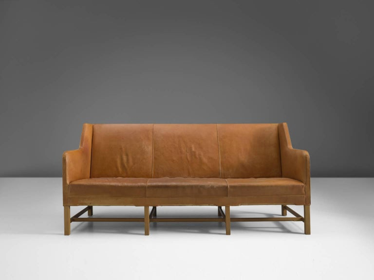 Sofa model 5011, in leather and oak, by Kaare Klint for Rud Rasmussen, Denmark 1935.   Classic and elegant Scandinavian three-seat sofa by Kaare Klint. This model was designed in 1935. The base consists of eight legs in oak with cross-connections,