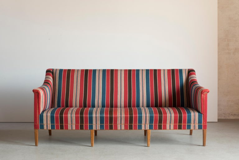Kaare Klint three seat sofa with eight legs of Mahogany. Seat, sides and back upholstered with blue, red and white striped