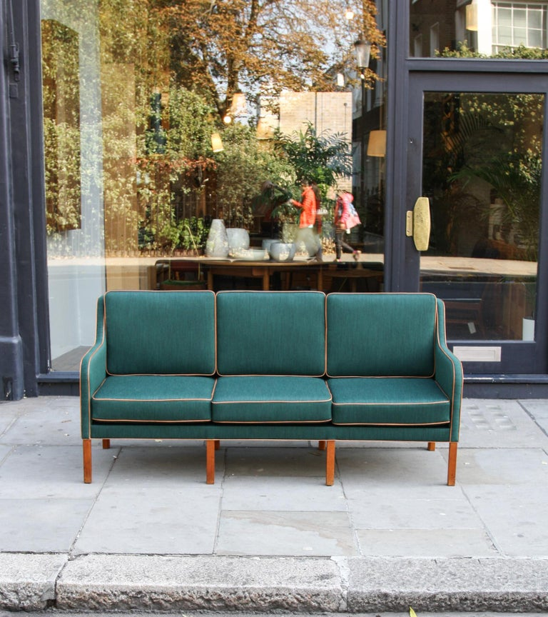 A vintage three-seat sofa by Kaare Klint, Denmark, 1940s. Reupholstered in a radiant green fabric with cognac leather trim, the sofa stands on eight solid mahogany legs and has six copper springs coiled cushions, which confers the sturdiness and