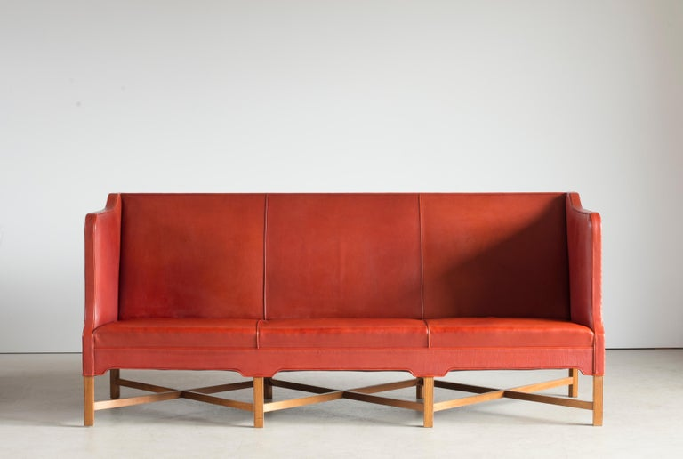 Kaare Klint freestanding three-seat sofa on eight-legged, profiled mahogany cross-frame. Sides, seat and back upholstered with patinated red leather. Model 4118. Executed by Rud. Rasmussen, Nørrebrogade, Copenhagen.