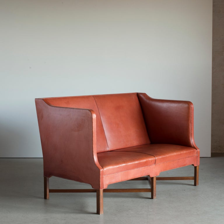 Kaare Klint freestanding two-seat sofa on six-legged, profiled mahogany cross-frame. Sides, seat and back upholstered with patinated leather. Executed by Rud. Rasmussen, Copenhagen.