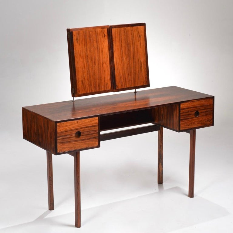 Vanity designed by Kai Kristiansen for Aksel Kjersgaard in the mid-1960s, model 40. Solid rosewood drawer fronts with striking round recessed pulls. The mirror angle adjusts by sliding the rosewood cubes up and down the mounting posts. Great