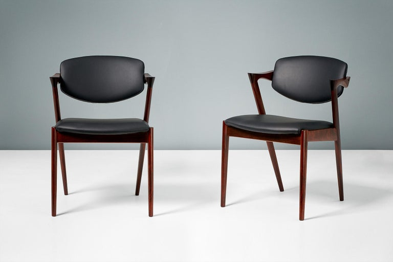 Kai Kristiansen  Model 42 dining chairs, 1956.  Set of 8 dining chairs produced by Skovman Andersen for the Illum Bolighus department store in Copenhagen. Refinished rosewood frames with seat and back reupholstered with premium black leather.
