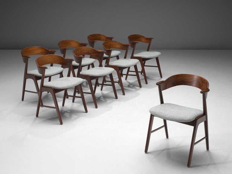 Set of eight dining chairs, rosewood, fabric, Denmark, 1950s.   The chairs show beautiful and well designed lines and joints. The curved back and armrests are mounted on the oblique rear legs, which provides an open, light expression. A nice grain