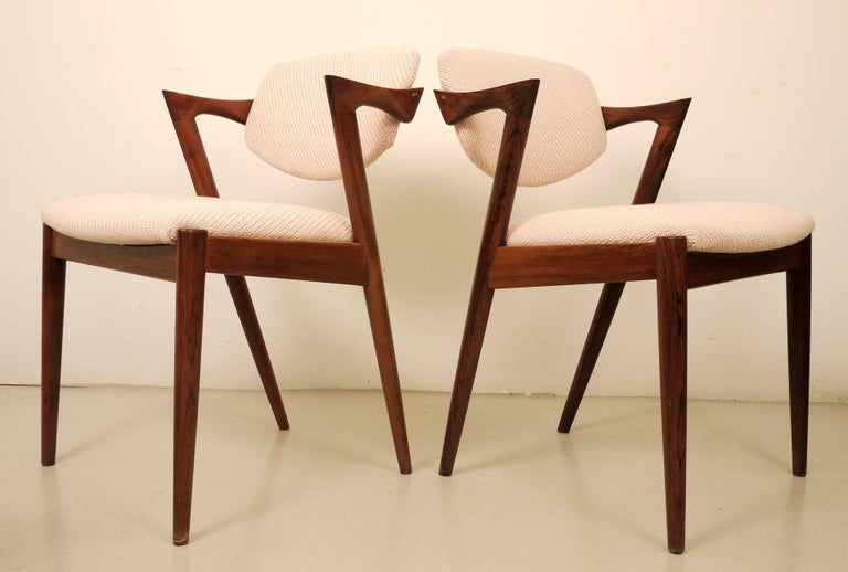 A set of six Kai Kristiansen rosewood dining chairs. Edited by Schou Andersen Mobel in the 1960s. Fully refurbished and reupholstered in off-white weave Kvadrat Coda Fabric. Pivot backrests. Excellent.