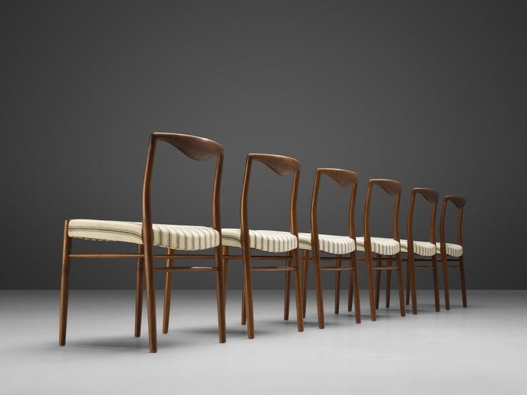 Kai Lyngfeldt Larsen for Søren Willadsen Møbelfabrik, set of six dining chairs, teak, off-white fabric, Denmark, 1960s  These elegant, curvy dining chairs show wonderful craftsmanship. The top rail is formed by a sculptural piece. The organic teak