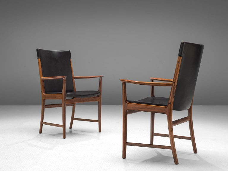 Kai Lyngfeldt Larsen for Søren Willadsen, pair of armchairs, rosewood and black leather, Denmark 1950s.   Elegant dining chairs with armrests. These majestic chairs have a rosewood frame with a beautiful visible grain. Nicely curved armrests and