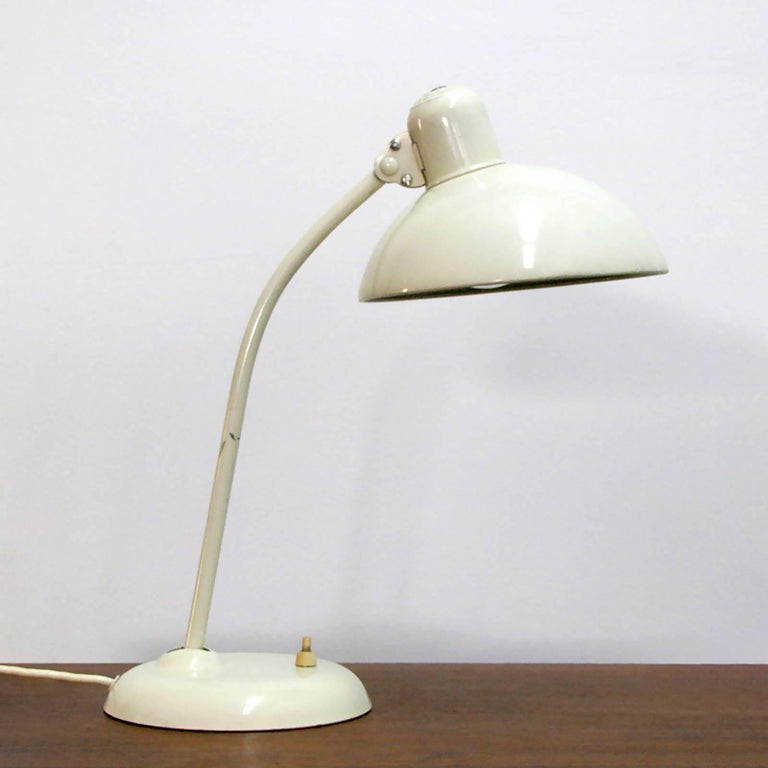 Original ivory enameled steel desk/ task lamps model '6556' by Christian Dell for Kaiser Idell, with a curved pivoting arm and a broad dome shade, marked. Priced individually.