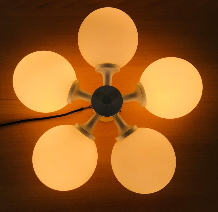 A midcentury flush mount by Kaiser made in Germany in the 1960s. It is fascinating with its Space Age design and five opaque balls. The white circular body of the light is made of full metal, including the arms.