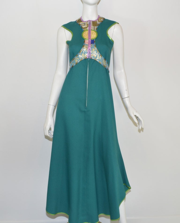 Kaisik Wong Teal Ensemble with Jacket & Dress -- Dress is featured in a teal blue with a metallic lame design along the bust and neckline and a front zipper closure. Jacket has a multicolored lame design along the opening and around the hem with