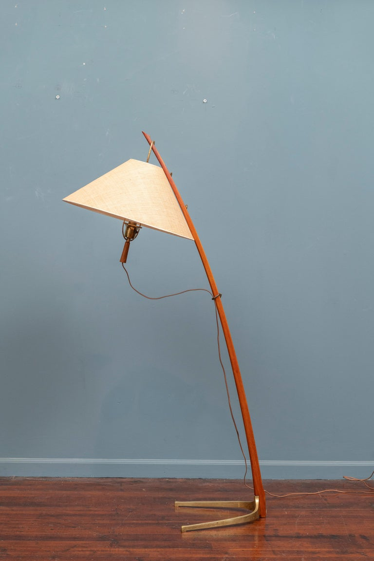 A beautiful Dornstab ('thorn stick') floor lamp, designed in 1947 by J.T. Kalmar. It is made out of a wooden, saber shaped stem with a curved brass base and fabric shade. The height of the shade is adjustable to three different positions on the