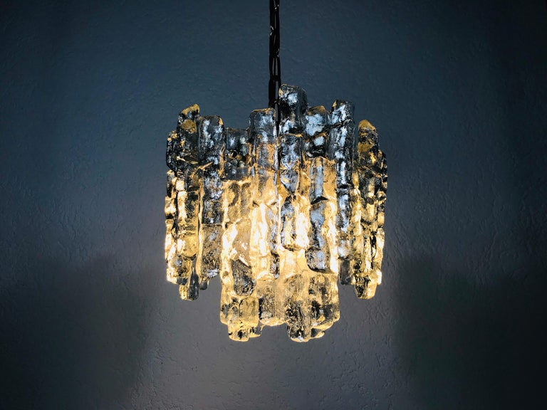This is a beautiful ice glass chandelier from Kalmar Franken made in Austria in the 1960s. It is a fascinating lighting with a beautiful design. The frame and the chain are of full brass. Two-tier ice glass shade.   Measurements:  Total height: