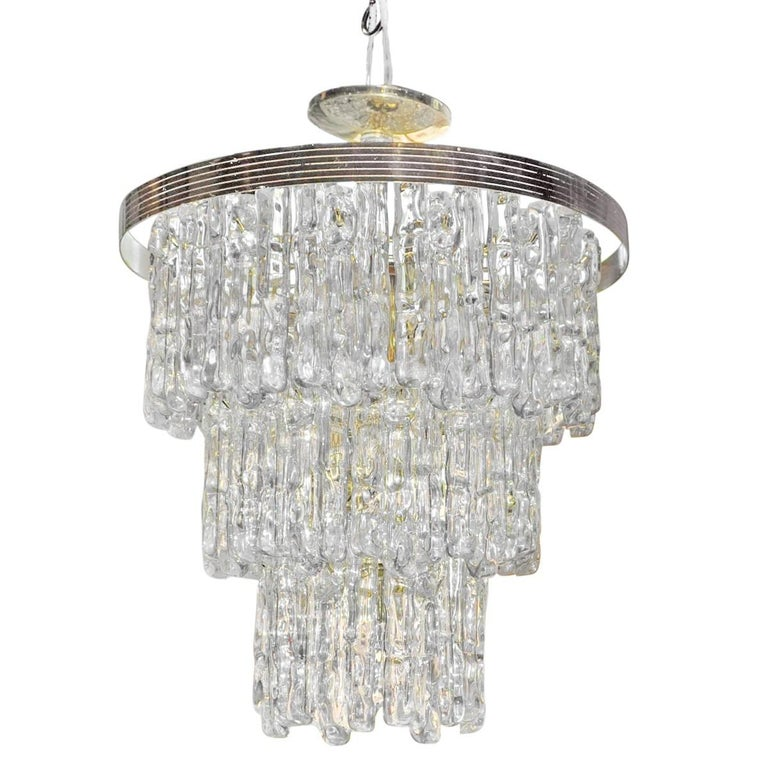 Italian Hollywood Regency style modern three-tiered waterfall chandelier with gold brass frame and ice-like Lucite/acrylic prisms. Original wiring in working condition. Eight candle base bulbs. 40 watts each. Brass-plated canopy included.   In the