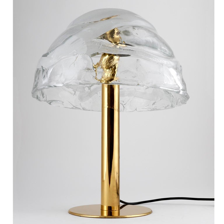 A brass and Murano glass table light model 'Dom' by J.T. Kalmar, Austria, manufactured in midcentury, circa 1970 (late 1960s or early 1970s). A large hand blown lampshade made of textured clear crystal glass with a white bubble spiral is held by a
