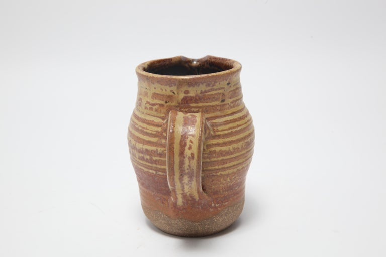 American Mid-Century Modern stoneware art pottery pitcher designed by Karen Karnes (American, 1925-2016), with an orange and ochre glaze. The piece is signed with an impressed artist's monogram