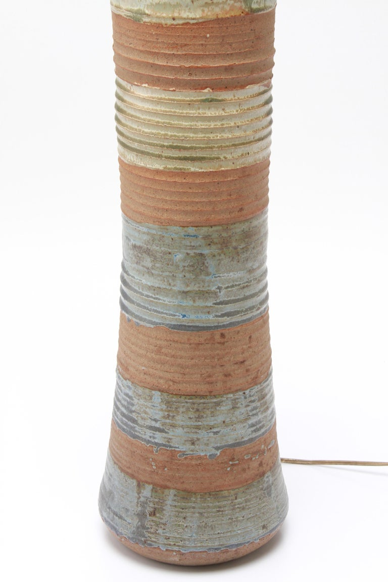 American Mid-Century Modern stoneware art pottery table lamp designed by Karen Karnes, (American, 1925-2016). The piece has a polychrome glaze with alternating horizontal bands and is signed with an impressed artist's monogram